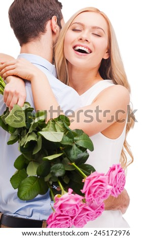 I love you so much! Beautiful young loving couple hugging while woman holding bouquet of pink roses and smiling and both standing isolated on white background   - stock photo