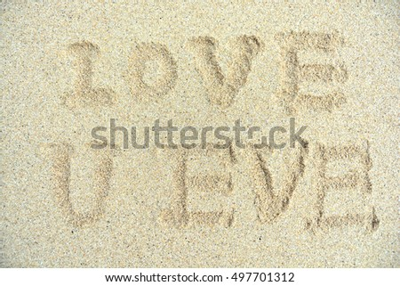 i love you written with finger on sandy beach