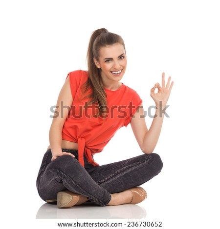 I'm fine. Smiling girl in red top, black jeans and high heels sitting on the floor and showing ok sign. Full length studio shot isolated on white. - stock photo