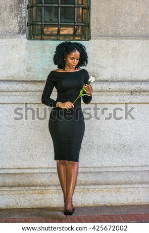 I missing you. African American Woman seeking love in New York, with braid hairstyle, wearing long sleeve, off shoulder dress, standing against wall on street, looking down at white rose, thinking. - stock photo