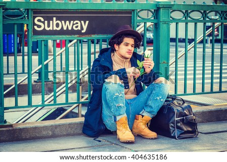 I missing you. Wearing jacket with hood, jeans, boot shoes, Fedora hat, leather bag on ground, a guy with freckle face, sitting on street by Subway sign in New York, looking at white rose, thinking.  - stock photo