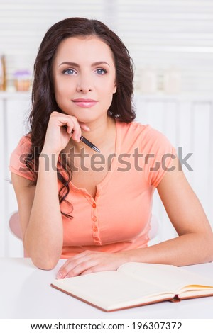 I need some fresh ideas. Beautiful young woman holding hand on chin and looking away while sitting at the table with note pad on it - stock photo