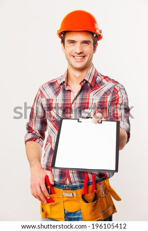 I need your signature here. Cheerful young handyman in hardhat holding stretching out clipboard with paper and smiling while standing against grey background - stock photo