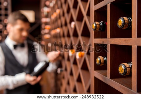 I recommend this wine. Confident male sommelier showing wine bottle and smiling while standing near the wine shelf  - stock photo