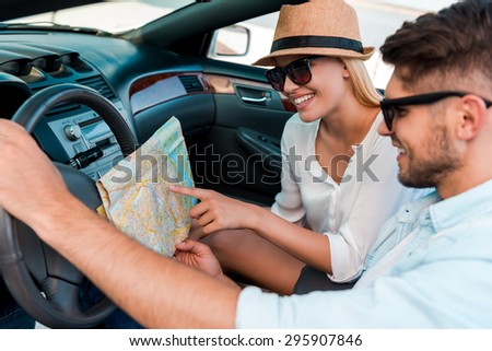 I think we should turn here. Happy young couple examining the map while sitting in their convertible  - stock photo