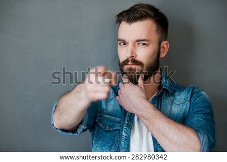 I think you must do it!Serious young man holding hand on chin and pointing you while standing against grey background - stock photo