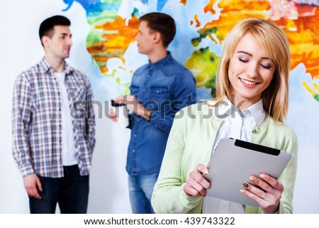 I use all opportunities to study hard. Confident young woman holding tablet  and looking at him with smile while his colleagues talking in the background.
