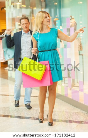 I want it all! Full length of mature couple shopping in shopping mall together while woman pointing mannequin