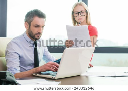 I want to be as my father. Confident young man in shirt and tie working on laptop while his little daughter sitting close to him and examining documents  - stock photo