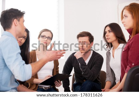 I want to share my problem. Group of people sitting close to each other while man telling something and gesturing - stock photo