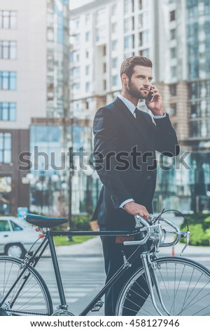 I will be in a time! Confident young businessman rolling his bicycle and talking on the mobile phone while walking outdoors - stock photo