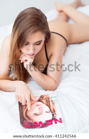I will be like you. Pleasant magnetic attractive woman lying in bed and resting while looking at the  magazine