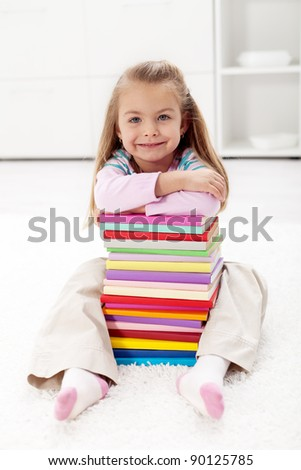 I will learn all this wisdom - little girl with lots of colorful books - stock photo