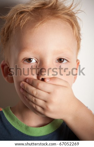 I will not tell! Little boy covered his mouth with his hand. - stock photo
