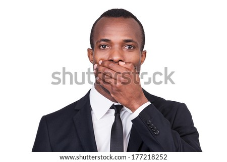 I will say nothing. Portrait of young African man in formalwear covering his mouth with hand while standing isolated on white background