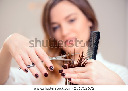 I will style you right. Selective focus image of beautiful hairdresser doing hairstyle to her client while standing on the background of a professional hairdressing salon - stock photo