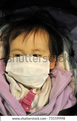 IBARAKI PREFECTURE, JAPAN-MAR 18:One year old Japanese girl Yuuna covered by a face mask protecting against radioactive dust in air after the Fukushima disaster Mar 18, 2011 in Ibaraki Prefect., Japan - stock photo