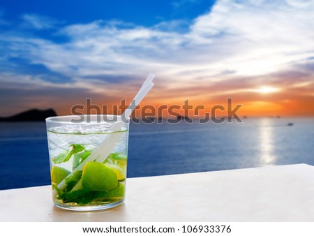 Ibiza cala Conta Conmte sunset with Mojito drink cocktail - stock photo