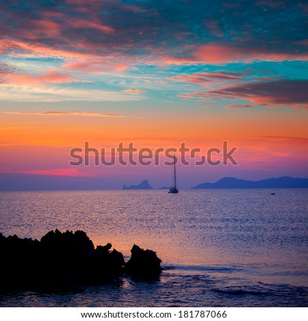 Ibiza sunset view from formentera Island with sailboat in Balearic Islands - stock photo