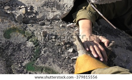 IBTIN, ISRAEL - DECEMBER 17, 2015: The hand of an injured soldier seeking help appears in the rubble after earthquake rocket attack tsunami drill