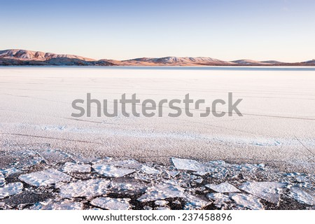 Ice and snow on the lake at sunset. Beautiful winter landscape. Creative toning effect - stock photo