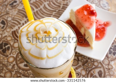 Ice blend caramel coffee with crape cake and strawberry sauce are background. Selected focus on coffee. - stock photo