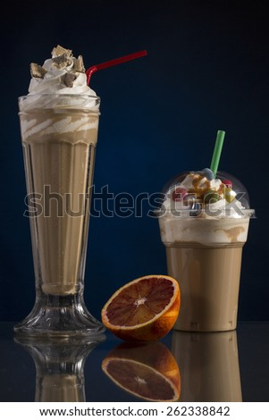 ice caffe in glass and plastic takeaway cup, decorated with whipping cream and bon-bons, advertisement for menu card - stock photo