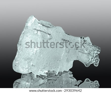 Ice. Chunk of ice on reflective surface - stock photo