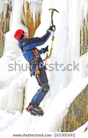 Ice climber reaching the summit - stock photo