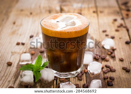 Ice coffee in a glass on the wooden table - stock photo