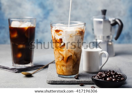 Ice coffee in a tall glass with cream poured over and coffee beans on a grey stone background - stock photo