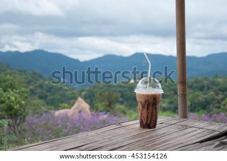 Ice coffee in plastic glass. good view in high hill. Mocha coffee take away - stock photo