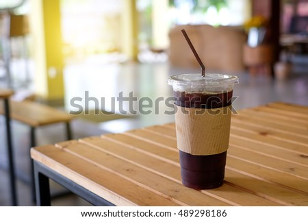 Ice coffee in plastic glass on wooden table with blurred background.
