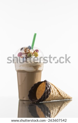 ice coffee in plastic take-away cup, decorated with whipping cream and bon-bons, advertisement for menu card - stock photo