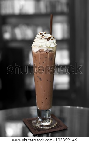 Ice coffee on top with whip cream and chocolate caramel with bookshelf background - stock photo