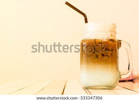 Ice coffee separate layer coffee and milk on wood table with soft focus and soft light orange warm tone - stock photo