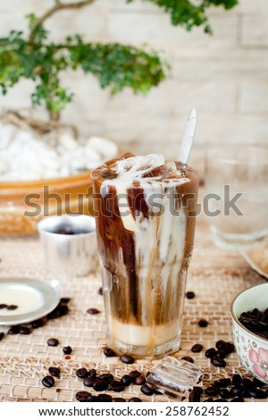 Ice coffee with condensed milk, traditional Vietnamese, Thai  coffee with coffee beans on a wooden background - stock photo