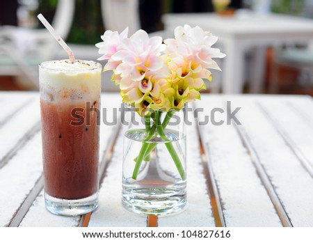 Ice coffee with flower on table. - stock photo