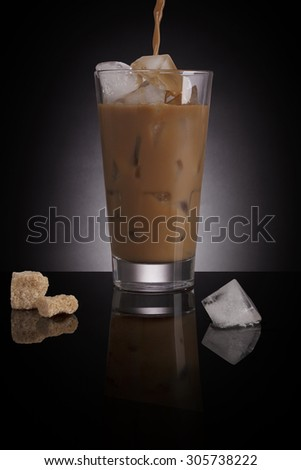 Ice coffee with melting ice cubes and brown sugar on dark background. Culinary gourmet luxurious coffee drinking. - stock photo
