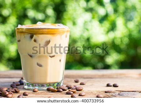 Ice coffee with milk on the wooden table - stock photo