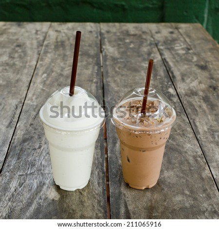 Ice coffee with milk shake on wood table - stock photo