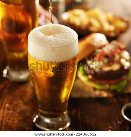 ice cold beer pouring into glass with burgers at restaurant table - stock photo