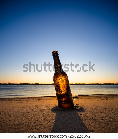 Ice cold brown bottle of beer / soda standing upright in the golden sand. Summer evening  - stock photo