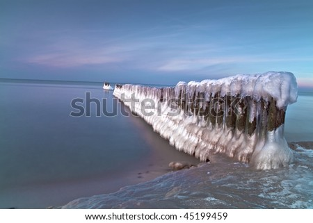 Ice-covered breakwaters and sunset over sea