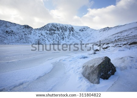 ice covered rock by frozen lake and snow covered mountains in helvellyn, cumbria - stock photo
