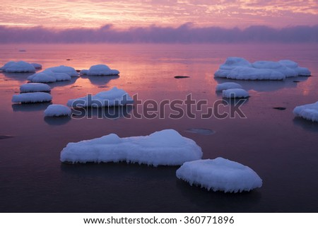 Ice-covered stones in still sea at sunset on a freezing cold day, vapor hiding horizon. Photographed at Baltic sea, Estonia. - stock photo