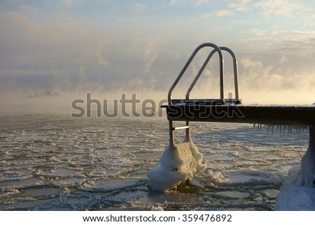 Ice covered swimming jetty and buoy in the freezing Baltic Sea in Helsinki, Finland just hours before complete freeze over of the sea on an extremely cold January morning (-20C) on 6 January 2016.  - stock photo