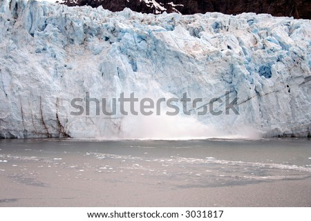 Ice crashing into the water below from glacier calving.