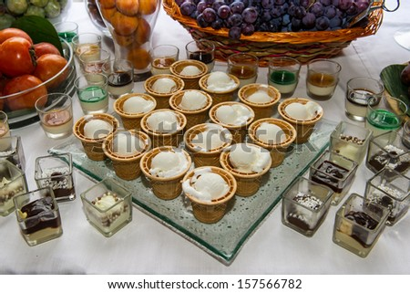 ice cream and mixed fruits with chocolates on white table for a dinner party