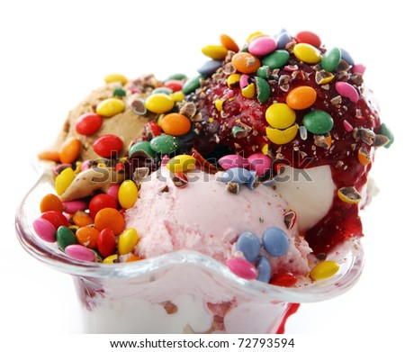 Ice cream dessert with colorful candies on white background